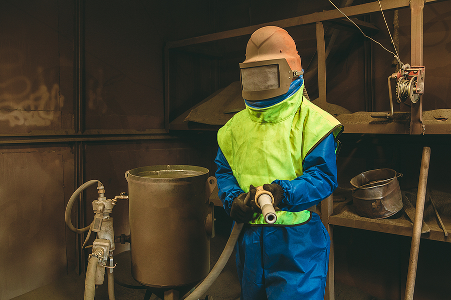 An employee prepares a metal part for sand blasting