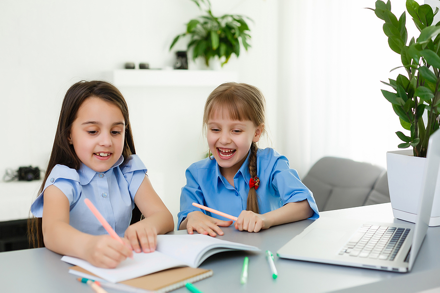Two little girls answering their worksheets
